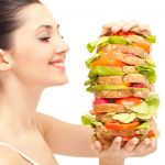 Pretty woman looking at nutrient rich sandwich