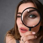 Pretty woman examining thyroid hormone replacement by looking through a magnifying glass